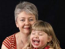 Mother and smiling daughter. Portrait of middle aged mother with laughing daughter, isolated on black background Stock Photo
