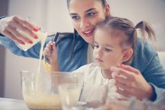 Mother and smiling girl baking cookies together. Close up stock image