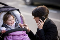 A mother smiling at her baby, talking on her mobile phone Stock Images
