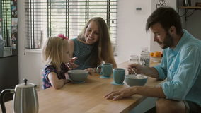 Mother is smiling at her daughter while having conversation with husband at the kitchen table. Slow mo, Steadicam shot stock footage