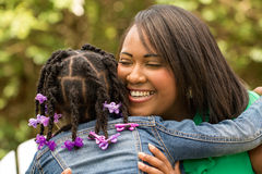 Mother smiling and hugging her daughter royalty free stock photos