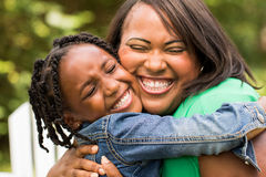 Mother smiling and hugging her daughter royalty free stock photo