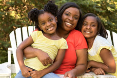 Mother smiling and hugging her daughters Royalty Free Stock Image