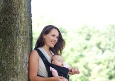 Mother smiling with infant in baby carrier Stock Images