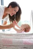 Mother smiling with infant child in bed. Close up portrait of a mother smiling with infant child in bed Stock Photography
