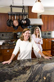 Mother smiling in kitchen with teenage daughter Stock Photography