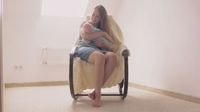 Mother smiling at newborn son lulling him in a rocking chair. 4k stock footage