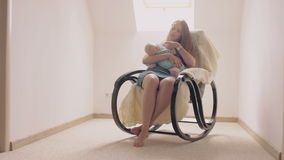 Mother smiling at newborn son lulling him in a rocking chair. 4k stock video footage