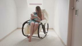 Mother smiling at newborn son lulling him in a rocking chair. stock video