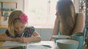 Mother is smiling while talking to her little daughter who is colouring a picture on the kitchen table. Slow mo stock video