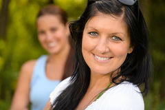 Mother smiling with teen daughter in background Royalty Free Stock Photography
