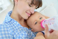 Mother snuggling baby during feed. Baby royalty free stock photo