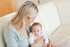 Mother on the sofa with her newborn on her lap Royalty Free Stock Photo