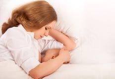 Mother som matar henne, behandla som ett barn i sängen. sova tillsammans Royaltyfria Foton