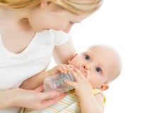 Mother som matar henne, behandla som ett barn pojken som spädbarn från buteljerar Arkivfoto