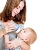 Mother som matar henne som är gullig, behandla som ett barn pojken från buteljerar Royaltyfri Bild