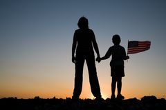 Mother and son. Mother holding her son and son holding an American flag at sunset Royalty Free Stock Photos