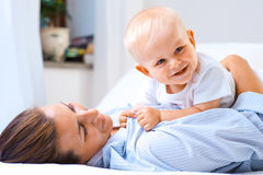 Mother and son. Young mother with her baby son on bed Royalty Free Stock Image