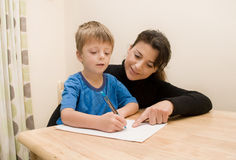 Mother and Son. Mother helping her son with writing Stock Photos