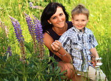Mother and son. On a big green colorful green grass meadow. spring and summer sun Stock Image