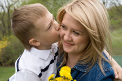Mother and son. Son kisses mother. In his hand the boy flower dandelion Royalty Free Stock Photo