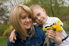 Mother and son. In his hand the boy flower dandelion Royalty Free Stock Image