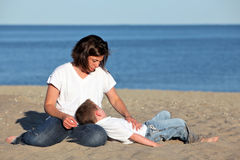 Mother and son. Pretty mother comforting tired son at the beach Royalty Free Stock Photography