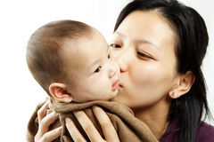 Mother and son. A mother kissing her cute baby son Stock Photography