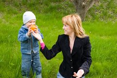 Mother and son. Mom and the son play with an orange on a grass. Spring Royalty Free Stock Photos
