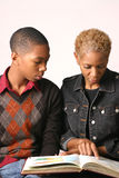 Mother and Son. Mother and teenage son review school assignment in open book Stock Photography