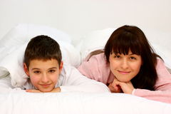 Mother and son. In bed smiling covered with white blanket Stock Photography