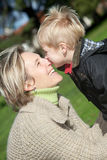 Mother and son. Little boy kissing his mother outdoors Royalty Free Stock Photography