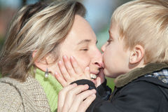 Mother and son. Close up of a little boy kissing his mother Stock Images