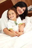 Mother and son. Happy mother hugging his son in bed royalty free stock photo