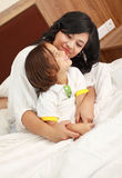 Mother and son. Happy mother hugging his son in bed Stock Photos