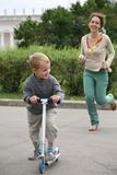 Mother and son. Mother runs after the son on the bicycle stock photos