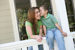 Mother and Son. A young boy kissing his pretty mother on the cheek Stock Photography