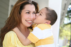 Mother and Son. A young boy kissing his pretty mother on the cheek Stock Images