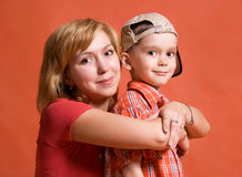 Mother and son. Loving mother and son embrace against orange background Stock Photography