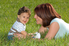 Mother and son. Smiling and Laying in Grass Stock Images