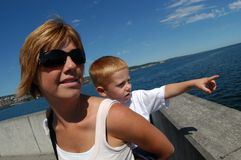 Mother and Son. On a warm, sunny afternoon standing at the end of a pier, a mother holds her son on her back as he points to a ship Stock Image