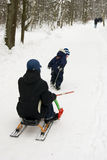 Mother and son. The little boy pulls sledges with mother on Royalty Free Stock Image