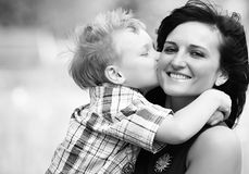 Mother and Son. Young attractive mum is holiding her child, a small boy, on her arms and is getting a big kiss from him. she is very happy Stock Photo