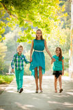 Mother with son adn daughter on a walk in park. In late summer afternoon royalty free stock photo