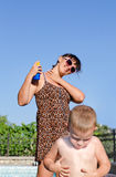 Mother and son applying suntan lotion Royalty Free Stock Photos