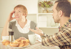 Mother and son arguing. Mature mother having disagreement with adult son at home Royalty Free Stock Photos