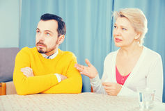 Mother and son arguing. Mature mother having disagreement with adult son at home Stock Images