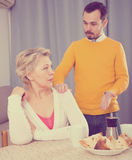 Mother and son arguing. Mature mother having disagreement with adult son at home Royalty Free Stock Image
