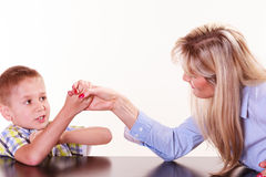 Mother and son arm wrestle sit at table. Royalty Free Stock Photography