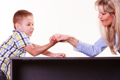 Mother and son arm wrestle sit at table. Stock Photo